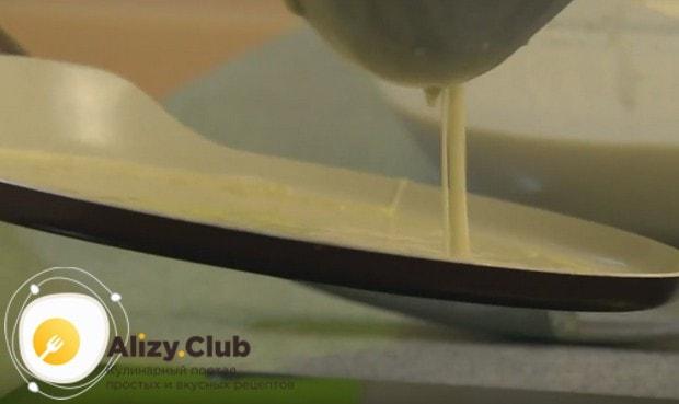 На разогретую и смазанную маслом сковороду наливаем половником тесто и формируем круглый блин.