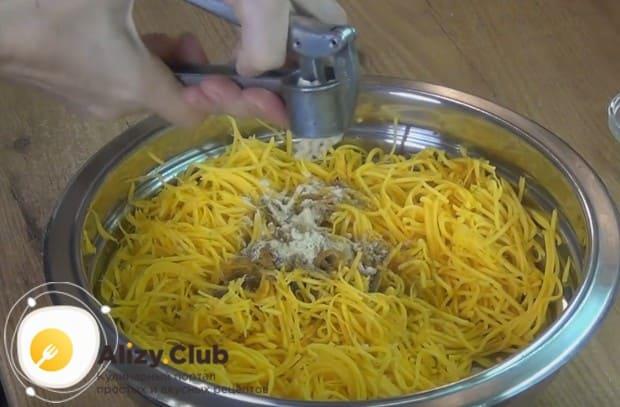 В натертую на корейской терке тыквы добавляем специи и чеснок.