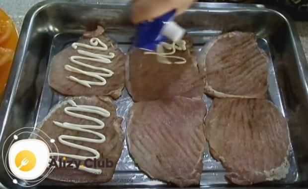 на смазанный растительным маслом противень выкладываем кусочки мяса, смазываем из майонезом.