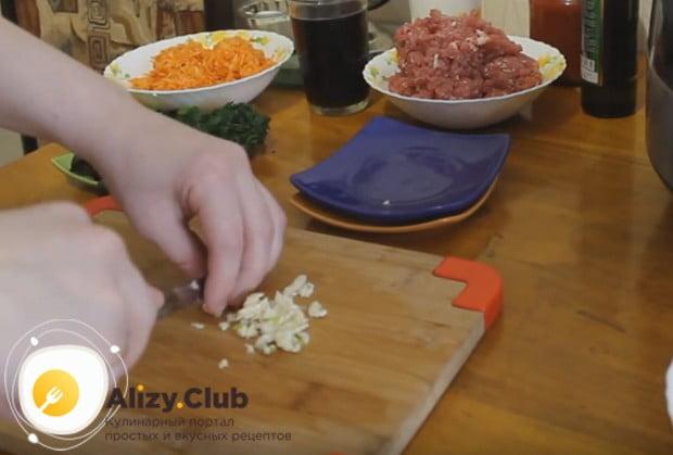 Измельчаем чеснок и добавляем вместе в сельдереем и луком в чашу мультиварки.