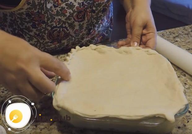 Обрезав лишнее тесто, защипываем края пирога.