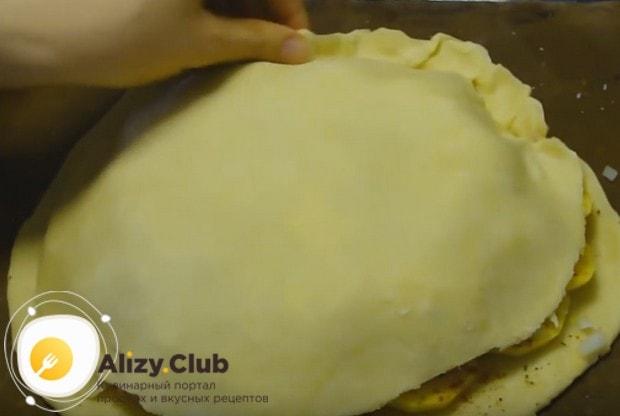Раскатываем второй кусок теста, накрываем ним начинку и защипываем края.
