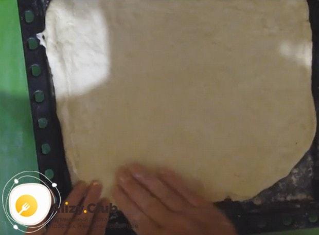 Одну часть теста выкладываем на противень, формируя основу для пирога.