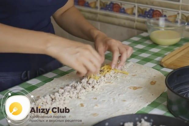 Раскладываем на столе лаваш, выкладываем на него часть начинки и посыпаем сыром.