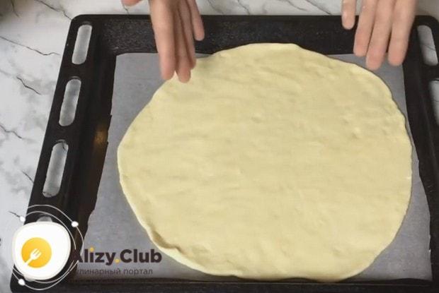Аккуратно перекладываем основу для пирог на застеленный пекарской бумагой пртивень.
