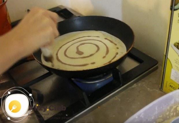 Налив на сковороду белый блинчик, кондитерским шприцем делаем спиральный узор тестом с какао.