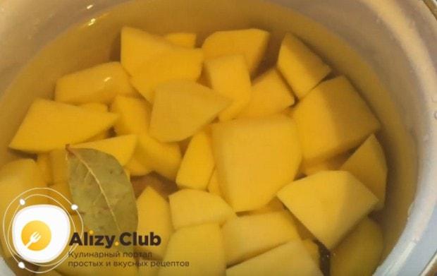 Выложив картошку в кастрюлю, заливаем ее водой и добавляем лавровый лист.