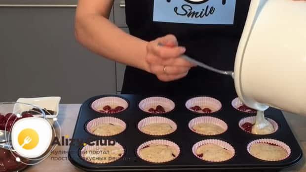 Для приготовления маффинов с вишней, выложите тесто на вишни.