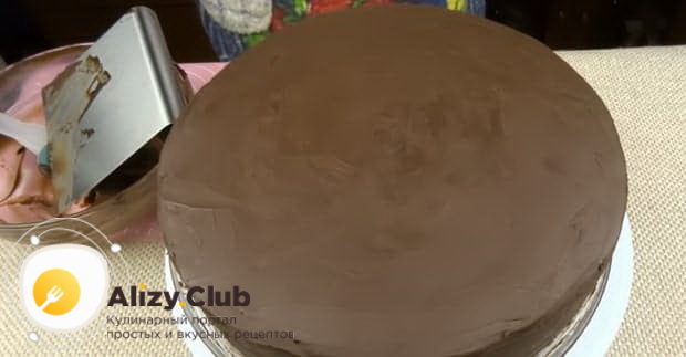 Нанесите ганаш для приготовления торта сникерс с безе.