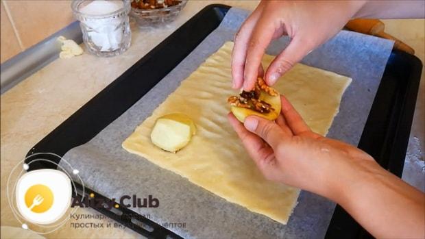Выложите яблоки с орехами на тесто для приготовления пирога с яблоками и корицей