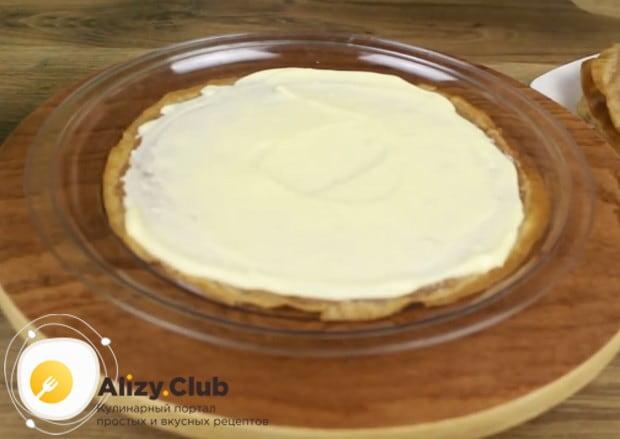 Выкладываем на блюдо блин, смазываем его кремом и накрываем следующим блином.