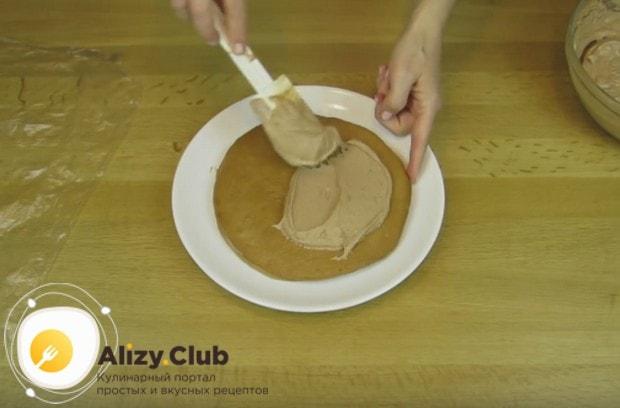 Переложив корж пропитанной стороной вниз на блюдо, смазываем его кремом.