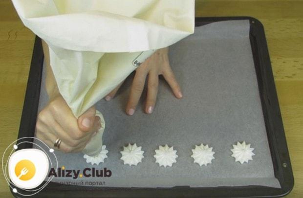 Переложив взбитый белок в кондитерский мешок, выкладываем на застеленный пергаментом противень безе.