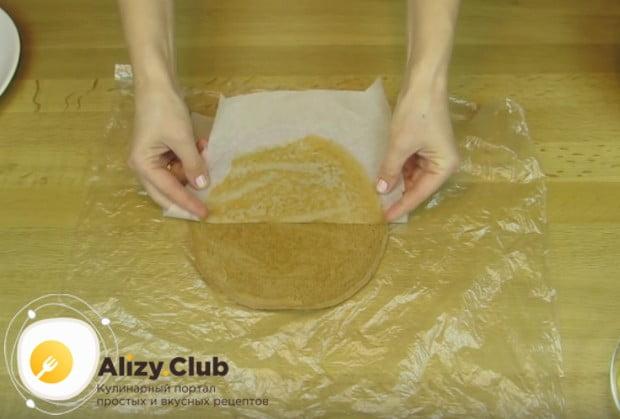 Аккуратно снимаем пергамент с коржей и перекладываем их на пищевую пленку.