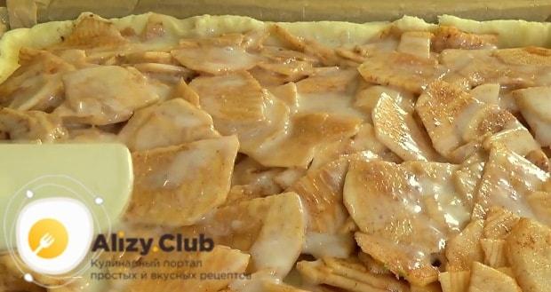 На остывшее тесто равномерно выложите яблочные кусочки
