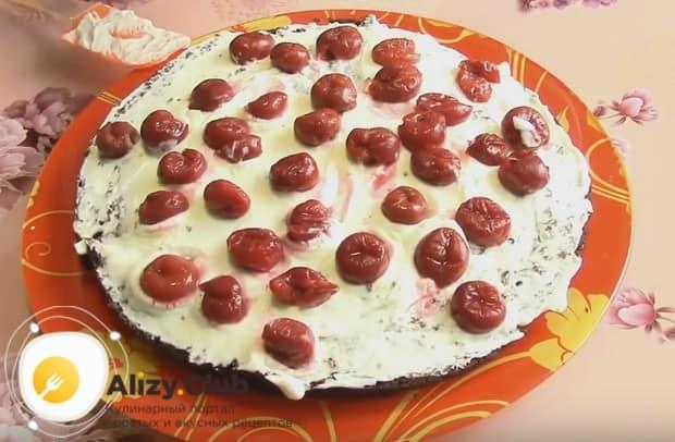 Покрываем первый корж для торта кремом, а сверху выкладываем вишни.