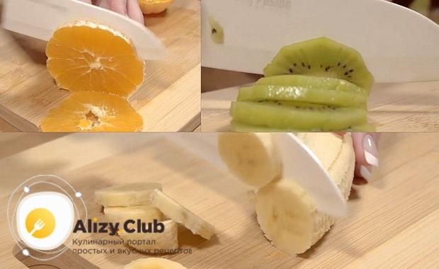 Нарежьте фрукты для приготовления торта из готовых бисквитных коржей со сгущенкой