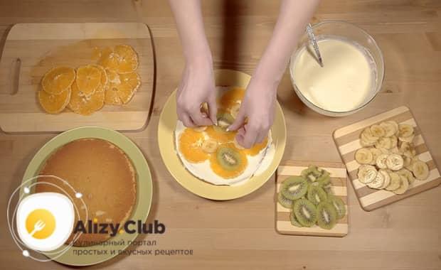 Положите фрукты на крем для приготовления торта из готовых бисквитных коржей со сгущенкой