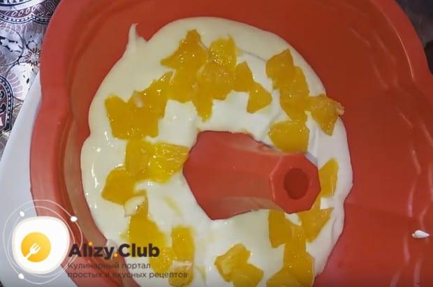 Поскольку мы готовим творожный торт без выпечки с фруктами, укладываем на крем нарезанный на кусочки апельсин.