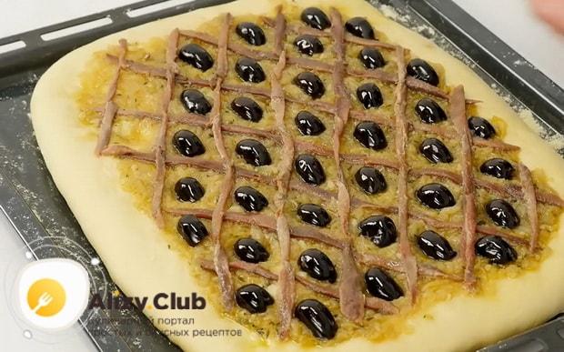 По рецепту, для приготовления французского лукового пирога выложите маслины на тесто.