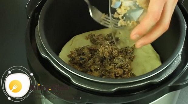 Выложите начинку на тесто для приготовления пирог с рыбными консервами в мультиварке.