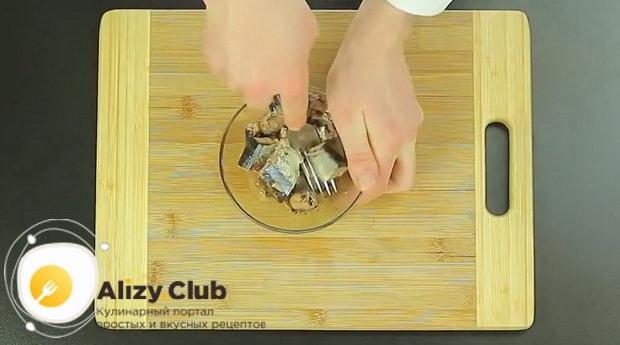 Измельчите рыбу для приготовления пирог с рыбными консервами в мультиварке.