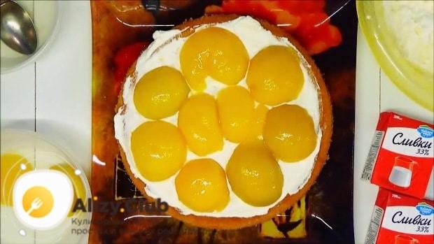 Смазываем корж кремом и выкладываем половинки персиков