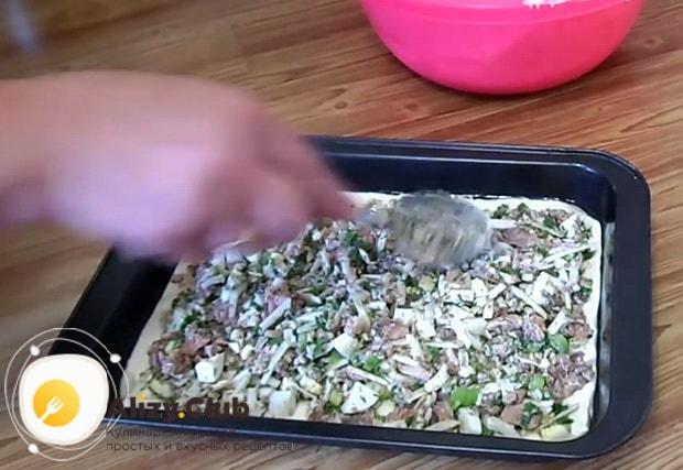 Заливной пирог с рыбными консервами на кефире выкладывается на противень слоями.