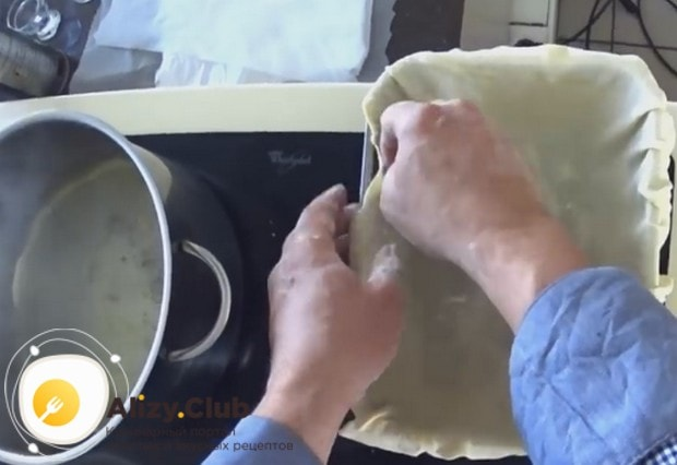 Укладываем раскатанное тесто в смазанную маслом форму для выпечки так, чтобы края немного свисали.