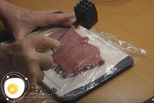 Затянув доску с мясом пищевой пленкой, немного его отбиваем.