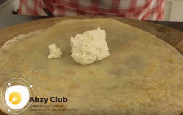 Выкладываем блинчик на блюдо и на центр его кладем немного начинки.