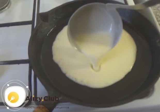 Половником наливаем на сковородку тесто и формируем круглый блин.