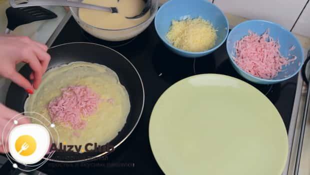 Для приготовления блинов с ветчиной и сыром выложите начинку.