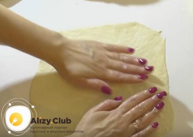 каждую часть теста аккуратно растягиваем руками на смазанной растительным маслом рабочей поверхности.