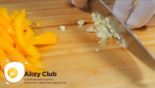 Для приготовления чахохбили из курицы в мультиварке нарежьте чеснок.