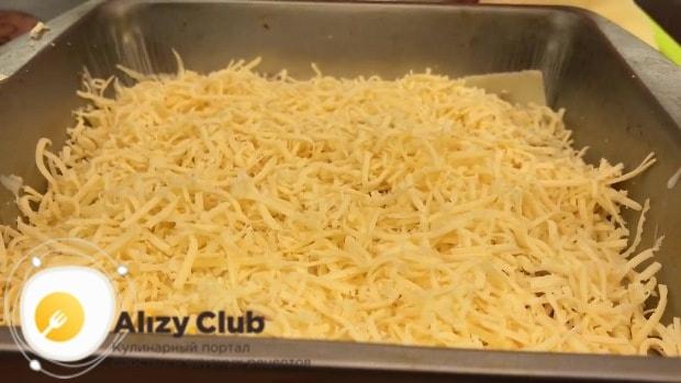 Пересыпьте первый слой лазаньи одной частью сыра