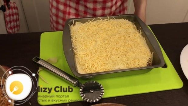 Последний лист теста залейте оставшимся белым соусом и пересыпьте сыром