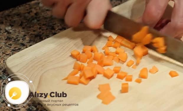 Для приготовления вкусного горохового супа с копченостями нарежьте морковь.