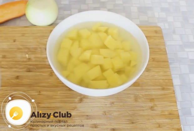 Нарезанную кубиком картошку кладем в миску и заливаем водой.