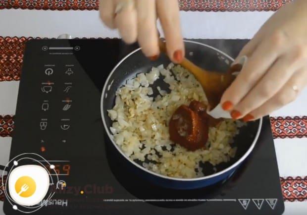 К луку добавляем томатную пасту, перемешиваем.
