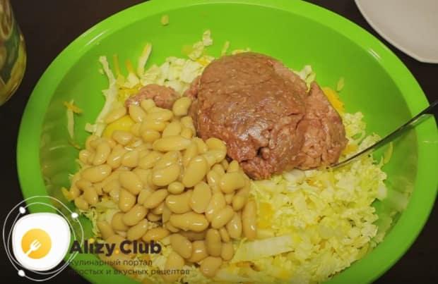 Перемешав овощи, выкладываем к ним мясной фарш, консервированную фасоль, а также выбиваем яйцо.