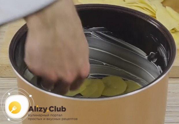 На дно красиво выкладываем половину подготовленного картофеля.