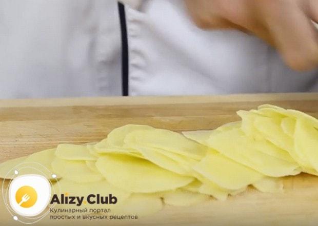 Тоненькими слайсами нарезаем картофель.