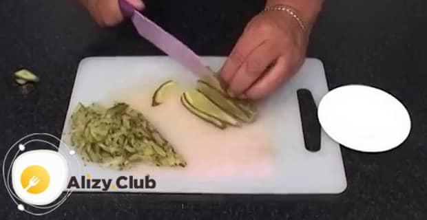 Для приготовления солянки из рыбы нарежьте огурец.