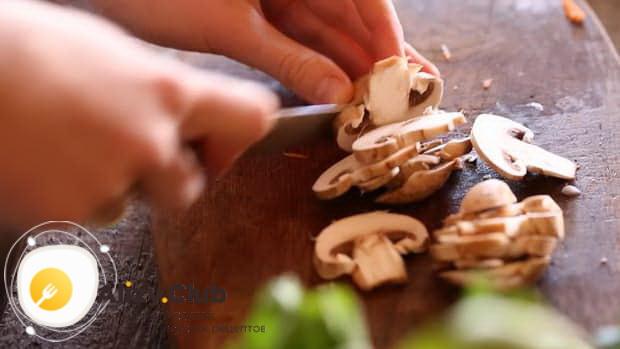 Нарежьте грибы для приготовления лазаньи без мяса