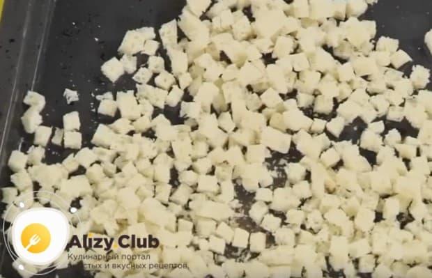 Режем кусочки батона мелким кубиком, складываем на противень и отправляем в духовку.