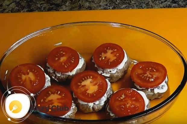 Формируем круглые котлетки, немного смазываем их майонезом, а сверху кладем кружочек помидора.