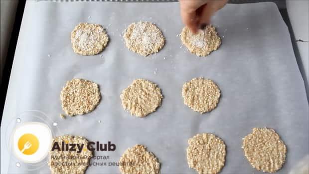 Выложите на кунжутное печенье кокосовую стружку.