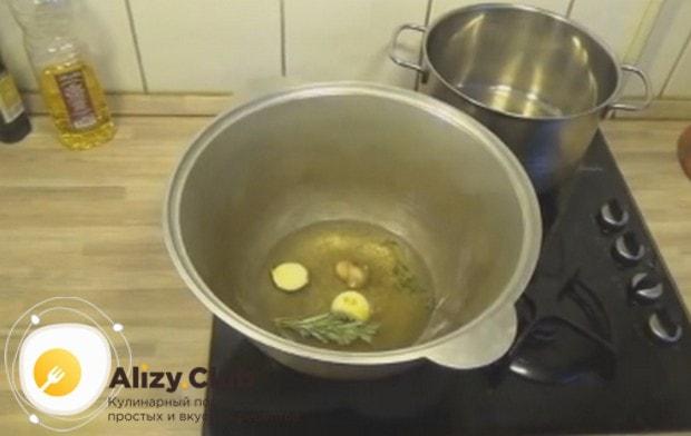 Разогреваем в казане растительное масло и кладем в него несколько зубчиков чеснока и веточки розмарина.