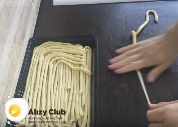 Вытягиваем лапшу, одновременно катая ее по столу другой рукой, чтобы изделие стало тоньше.